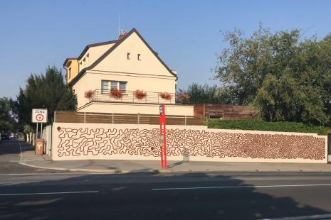 Mural art uautobusové zastávky Spořilov - motiv labyrintu, který průběžně zahuštěním klikatících se linií nabývá nasložitosti aobtížnosti, jezároveň silným dekorativním vzorem.